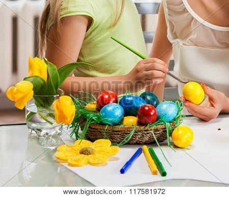 Children hands painting Easter eggs at home. Rainbow focus on eggs. Girl background.