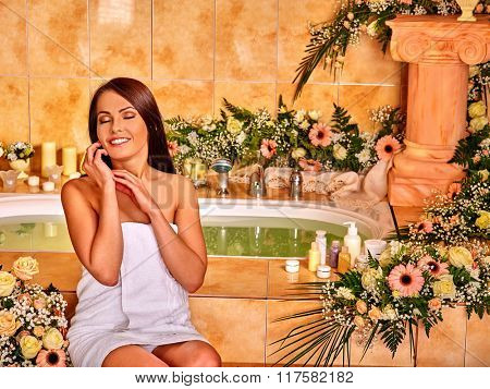 Woman relaxing at water spa. Girl sitting near  bath tub with water.