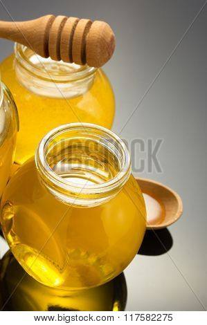glass jar full of honey on black background