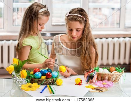 Sister iittle girl paint Easter eggs at home. Window background.