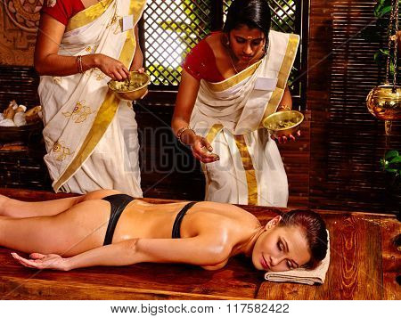 Young woman having body Ayurveda spa massage with two masseuses.