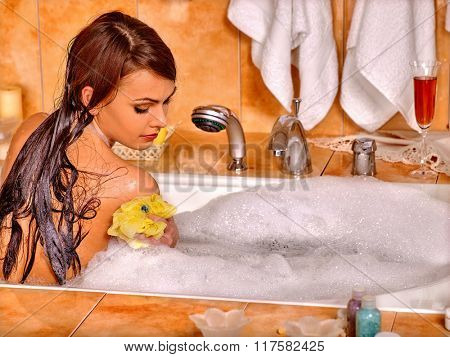 Young woman take bubble  bath. Woman washing her shoulder by yellow sponge.