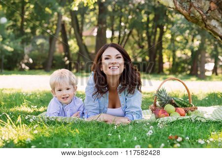 Young mother spending time with her son in the park having a picnic.