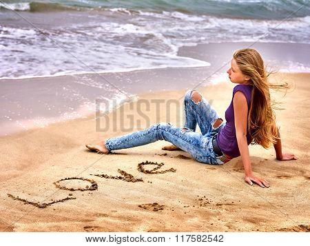 Summer girl sea.  Teenager writing love  on sand.