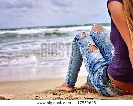 Summer girl sea.  Woman wearing in jeans with holes sitting on coast near ocean with waves. Hot dog leg selfie.