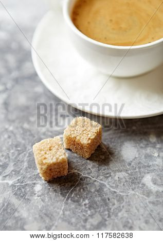 Two brown sugar cubes and a cup of coffee