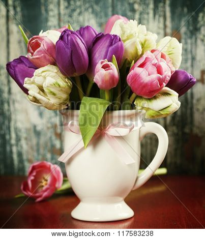 Beautiful tulips bouquet on old wooden table