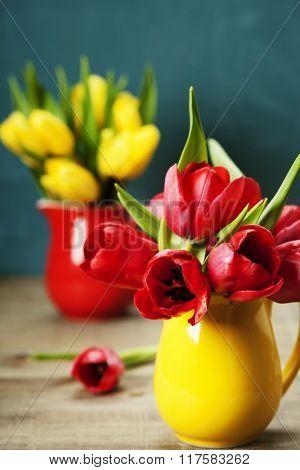 Spring tulips in vases  on wooden table - spring, easter or gardening concept