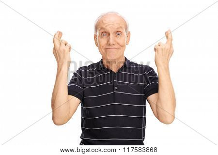 Studio shot of a senior man holding a his fingers crossed isolated on white background