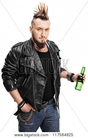 Vertical shot of a young male punk smoking a cigarette and holding a bottle of beer isolated on white background
