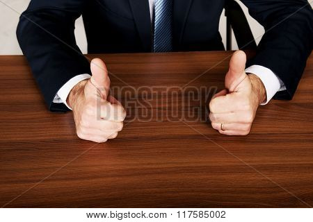 Closeup of businessman thumbs up on the desk