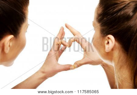 Two women making heart with fingers.