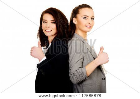 Two businesswomen with thumbs up.