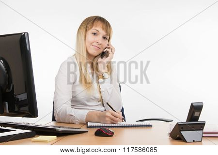 Happy Business Woman Talking On A Mobile Phone Writing In A Diary