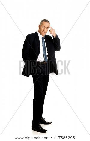 Full length businessman gesturing idiot sign