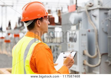 side view of electrical engineer writing on clipboard in substation