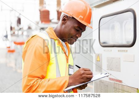 handsome African industrial technician taking machine readings