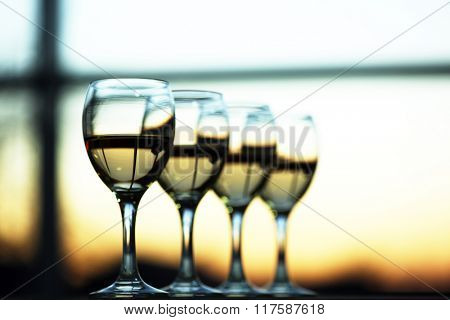 Row of wineglasses on light blurred background