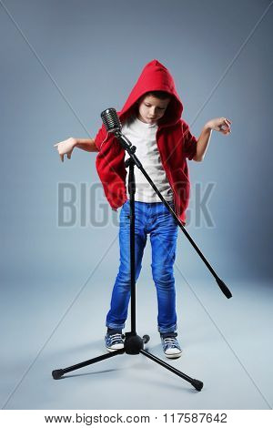 Little boy singing with microphone on a grey background