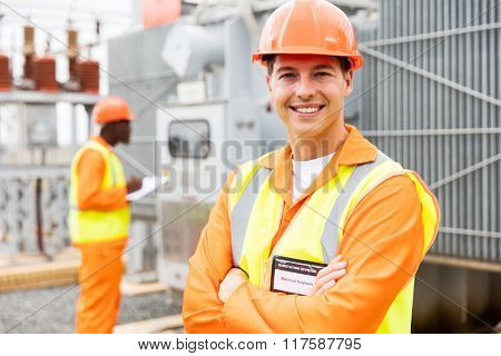 close up portrait of young electrical engineer with arms crossed in substation