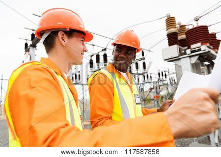 power company electricians discussing blueprint at electrical substation