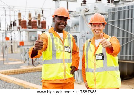cheerful technicians giving thumbs up in substation