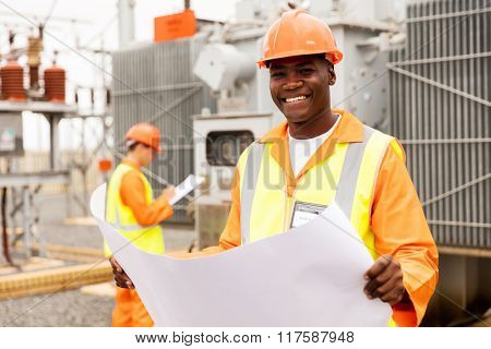 happy african american technician holding blueprint in substation