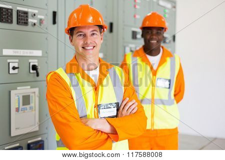 professional industrial electrician with colleague on background