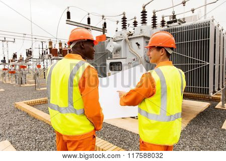 rear view of power company electrician working together in electrical substation