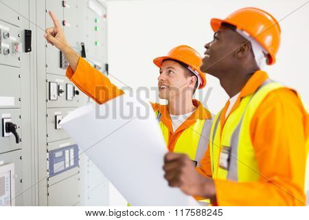 professional electricians working together in control room