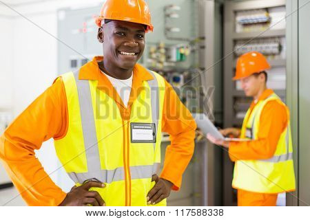 portrait of happy african industrial technician in front of colleague