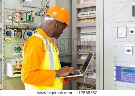 african american industrial engineer checking computerized machine status with laptop computer