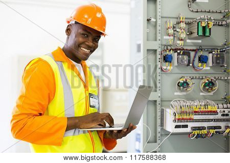 successful african electrical engineer using laptop checking machine status