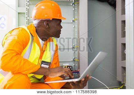 experienced senior african industrial technician checking machine status