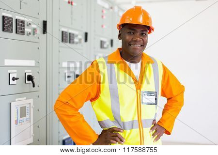 confident african electrician standing in power plant control room