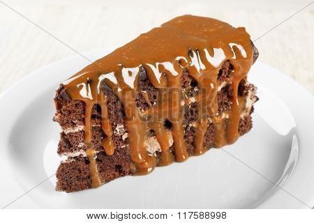 Piece of chocolate cake with caramel in white saucer close up