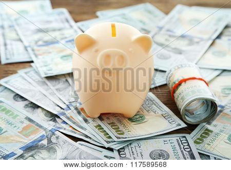 Piggy bank on pile of dollars background