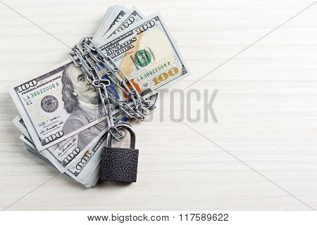 Dollars currency with lock and chain on wooden table background