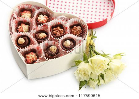 Heart shaped box with candies and flowers, close up