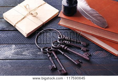 Bunch of old keys with notebooks on dark wooden background, close up