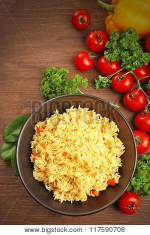 Stewed rice with a carrot on a black plate over wooden background