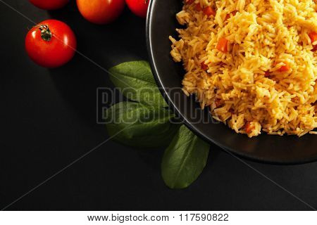 Stewed rice with a carrot and tomatoes on a plate over black background, close up