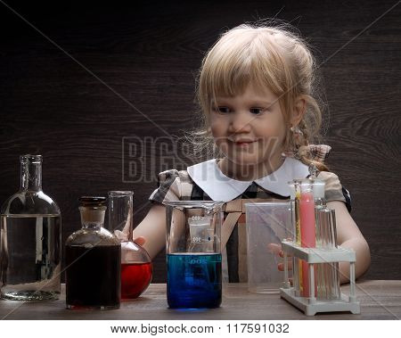 Small children spend experiments with chemical glassware and various liquids