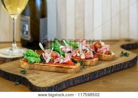 Appetizers - Tomato, Meat And Cheese On Wooden Board With Bottle Of Wine