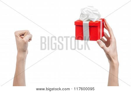 The Theme Of Celebrations And Gifts: Hand Holding A Gift Wrapped In Red Box With White Ribbon And Bo