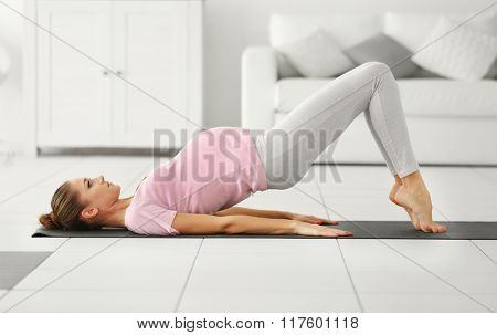 Health concept. Young beautiful pregnant woman does yoga exercise in the modern room