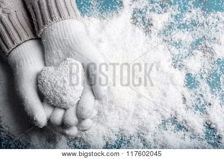 Female hands in mittens with heart on snow background