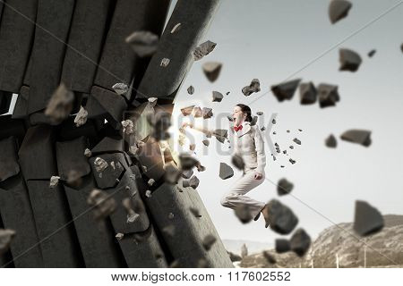 Businesswoman crashing bricks
