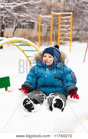 Cute Boy Sitting In Snow Outdoor
