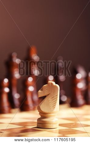 Chess pieces and game board on brown blurred background